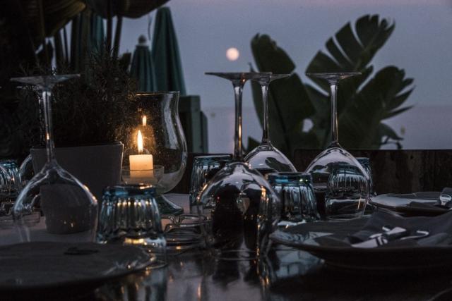 Romantic dinner table at sundown at Anjuna, a beach restaurant by the Mediterranean sea.