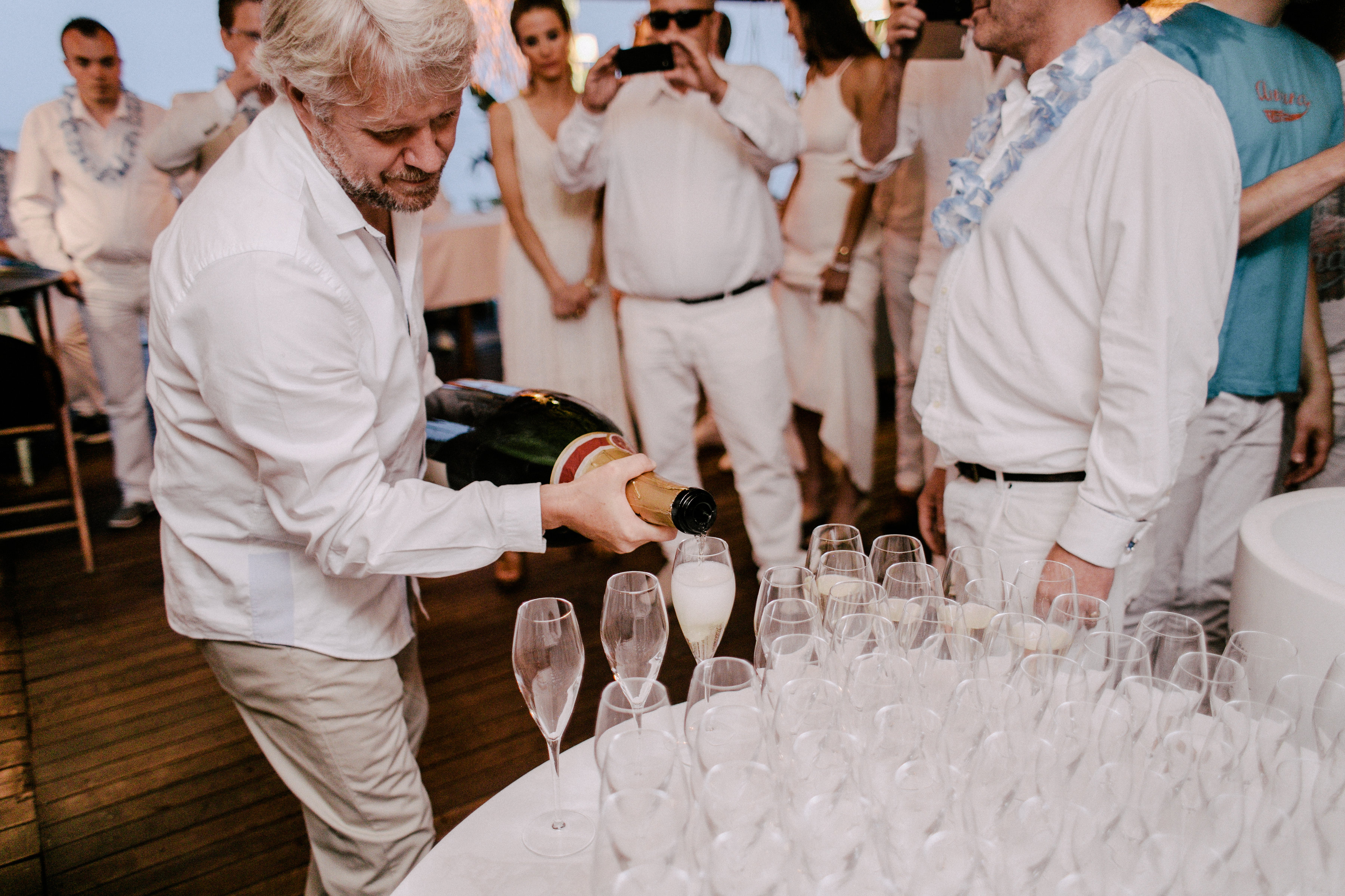 Champagne poured at a wedding reception at Anjuna, a beach restaurant by the Mediterranean Sea.